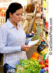 Shopping at the supermarket with a shopping list - Woman...