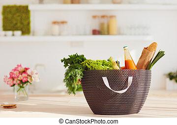 shopping bag full of fresh food on kitchen desk
