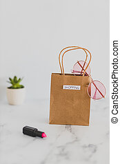 shopping bag on marble table top with mix of daily and stylish items around it