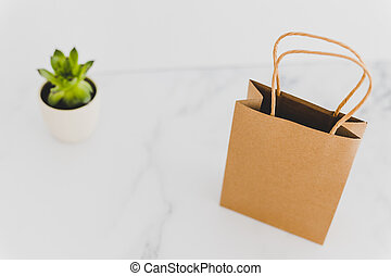 shopping bag on marble table top with succulent in the background