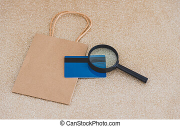 shopping bag with payment card and magnifying glass ...