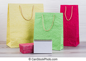 Shopping bags and blank paper notepad.