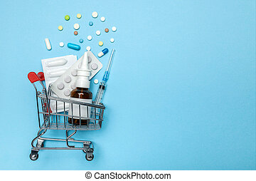 Shopping basket and pills in blisters, syringe and nasal spray. The concept of buying drugs online, delivery of medical devices. Copy space for text.