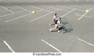 Shopping cart. A man and a woman with shopping carts run on the distillation to the store.