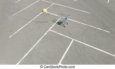 Shopping cart. A shopping cart stands in an empty parking lot.