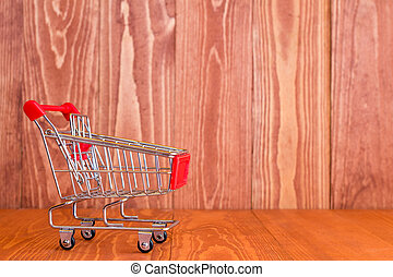Shopping cart against brown wooden background