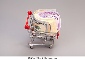 Shopping cart full of money (dollar, euro) isolated on gray background