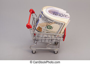 Shopping cart full of money (dollar, euro) isolated on gray background