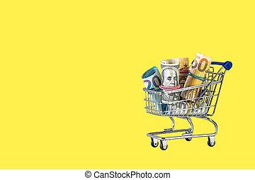 Shopping cart full of money isolated on Yellow background