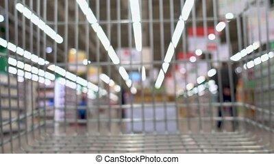 Shopping cart moving through big supermarket