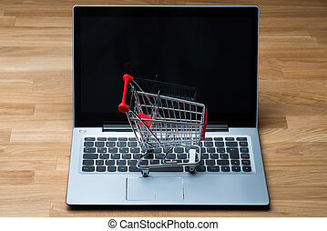 Shopping Cart On Laptop At Wooden Table