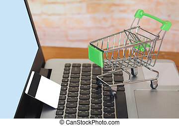 Shopping cart On Laptop Keyboard With Credit Card, Online Shopping Concept .