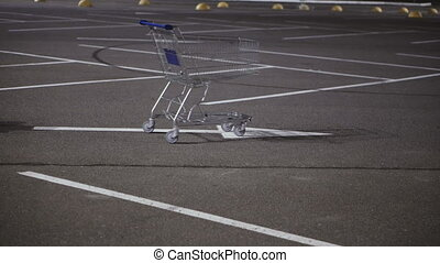 Shopping cart stands in the car parking