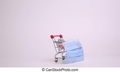 Shopping cart trolley with protective medical mask against coronavirus on white background. Stop motion animation. Safe online shopping on quarantine concept.