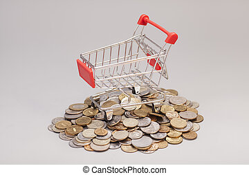 shopping cart with coins isolated on gray background