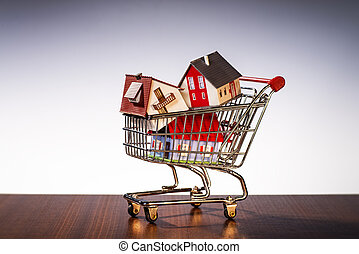 Shopping Cart with houses - Houses are stacked in a shopping...