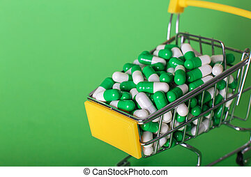 Shopping cart with medical pills on a green background