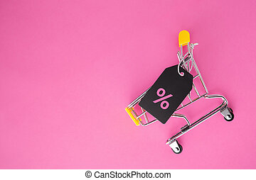 Shopping cart with sale tag on pastel pink background