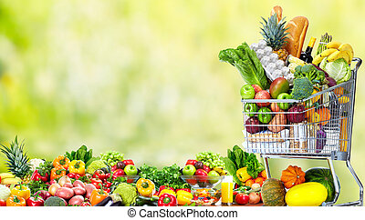 Shopping cart with vegetables and fruits. - Shopping cart...