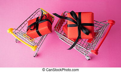 Shopping carts with red gift box on pink background