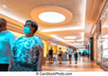 Shopping center interior blurred background. People shopping in modern commercial mall center. Interior of retail centre store in soft focus. Luxury inside business hall.