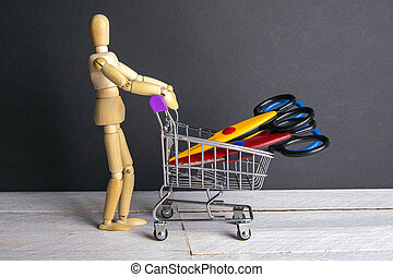 Shopping concept. Figure of a wooden man with a basket filled with stationery scissors