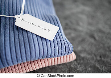shopping concept, knit jumpers in alternative colours with Fashion Trends text on price tag