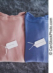 shopping concept, knit jumpers in alternative colours with Must Have and Fashion Trends text on price tag