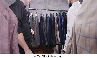 Shopping concept. Seller helps a young man to choose a suit in the store
