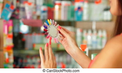 Young woman choosing nail polish in the beauty shop