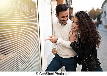 Shopping couple outdoors pointing at shop