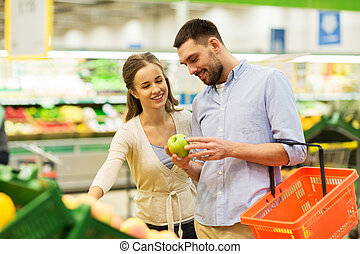 happy couple buying apples at grocery store