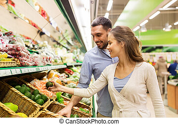 happy couple buying avocado at grocery store - shopping,...