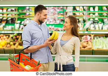 happy couple buying bananas at grocery store