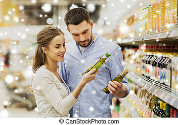 happy couple buying olive oil at grocery store - shopping,...