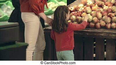 Shopping for Apples - Tracking shot of family coming up to ...