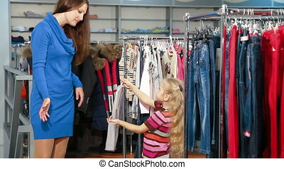 Mother and daughter shopping for girls clothes in a clothing store