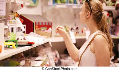 Young woman is choosing toys for her kid in the toy's store in the supermarket