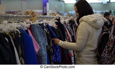 Girl at store looking for clothes to buy. Young woman shopping for clothing