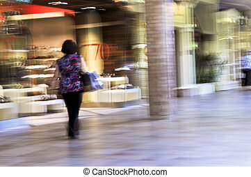 Shopping in a mall - Woman shopping in a mall, panning shot,...
