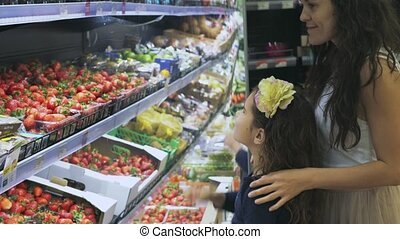 Shopping in the supermarket young mother with children