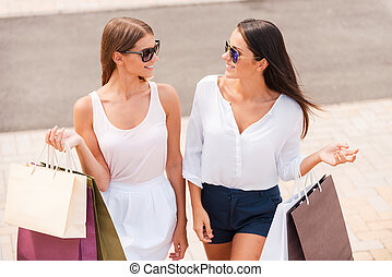 Shopping is the best therapy. Top view of two beautiful young women with shopping bags walking together and talking