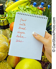 a woman holding a shopping list in a supermarket in the hand. english language.