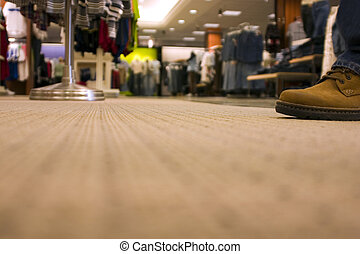 Shopping mall, man walking in front of the camera - floor view