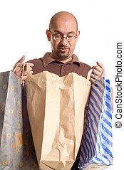 Shopping man - Young man holding bags and presents after...