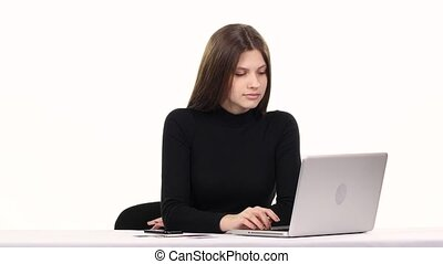 Shopping on the internet. Girl chooses product online. White
