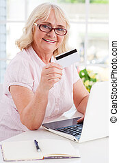 Shopping online. Happy senior woman using laptop and showing her credit card while sitting at the table