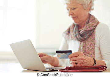 Grandmother using a credit card to make an online transaction