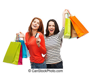 teenage girls with shopping bags and credit card - shopping,...