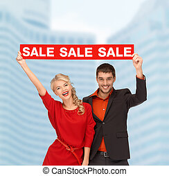 smiling woman and man with red sale sign - shopping, sale, ...
